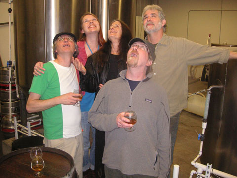 Band members posing together at a brewery looking up